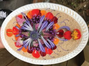 An oval platter with purple, pink, range and yellow flower petals arranged in a delicate pattern.