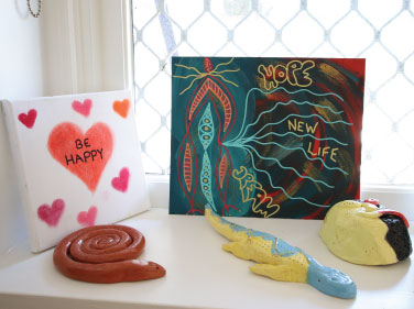 """A windowsill with art placed on it. There is a canvas with a love heart and the words """"BE HAPPY"""", alongside a terracotta coloured ceramic snake and a blue/yellow lizard."""