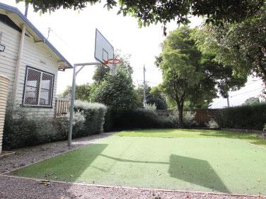 A garden area with a basketball hoop and garden beds.