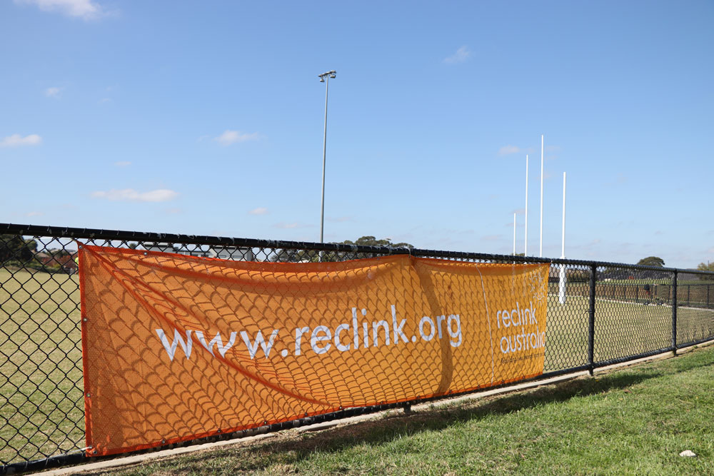 A football field on a sunny day, with goal posts to the right. An orange banner on the fence reads www.reclink.org and has the Reclink logo